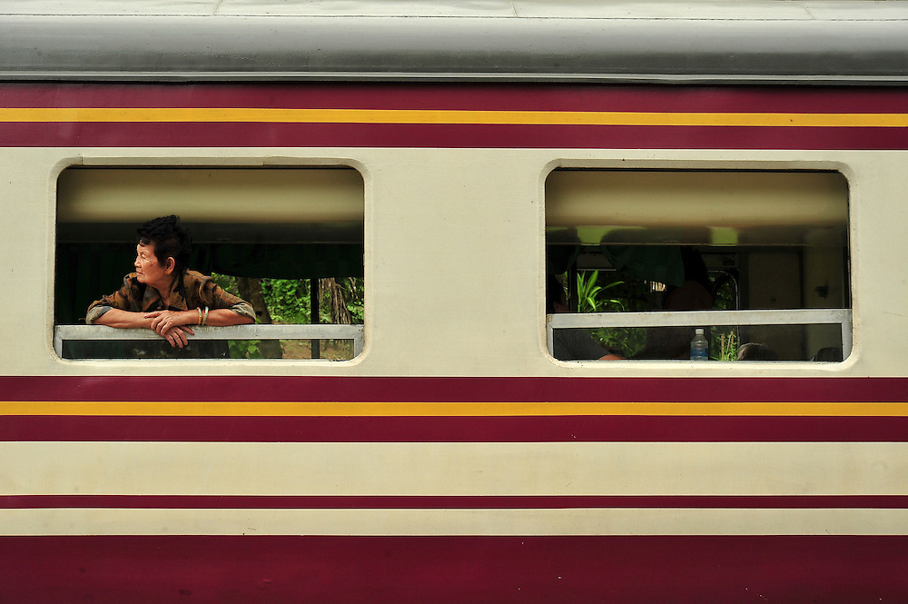 A woman peers out the window to see what is holding up this sleeper train travelling between the Thai capital city of Bangkok and the northern city of Chiang Mai.