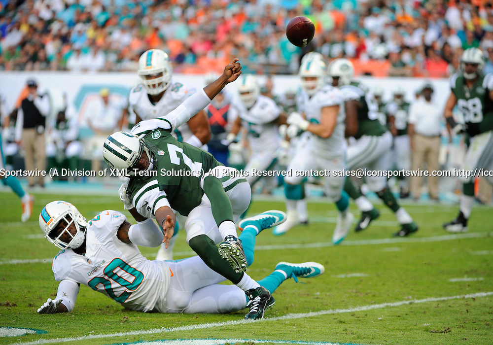 28 December 2014: New York Jets Quarterback Geno Smith (7) runs with ball and fumbles after knocking Miami Dolphins Safety Reshad Jones (20) to ground during the NFL football game between the New York Jets and the Miami Dolphins at the Sun Life Stadium in Miami Gardens, Florida.Miami Dolphins Linebacker Jason Trusnik (not shown) recovered the fumble.