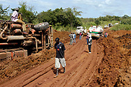 Overturned and stuck transport trucks along a road washed out by rains in Central Equatoria province. Decades of civil war have left the infrastructure of South Sudan in ruins.<br /> Liggi, South Sudan. 08/10/2009.
