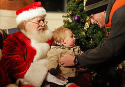Brad Harman, left, retrives his son Benjamin, 1, from Santa's (Jerry Swan) lap. Children came and had their photograph made with Santa and Mrs. Claus with the sounds of the University of Louisville Community Band in the background. (By Jonathan Palmer, Special to The Courier-Journal) December 6, 2008