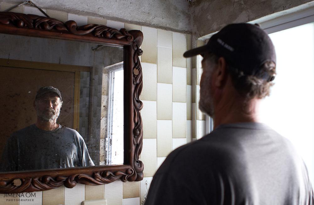 Fernando Güereña posa para un retrato frente al espejo cuyo marco resistió el paso del huracán Kenna y que fue labrado por su abuelo Eduardo Güereña, pionero de la pesca artesanal ribereña en Jalisco y constructor de barcos pesqueros.