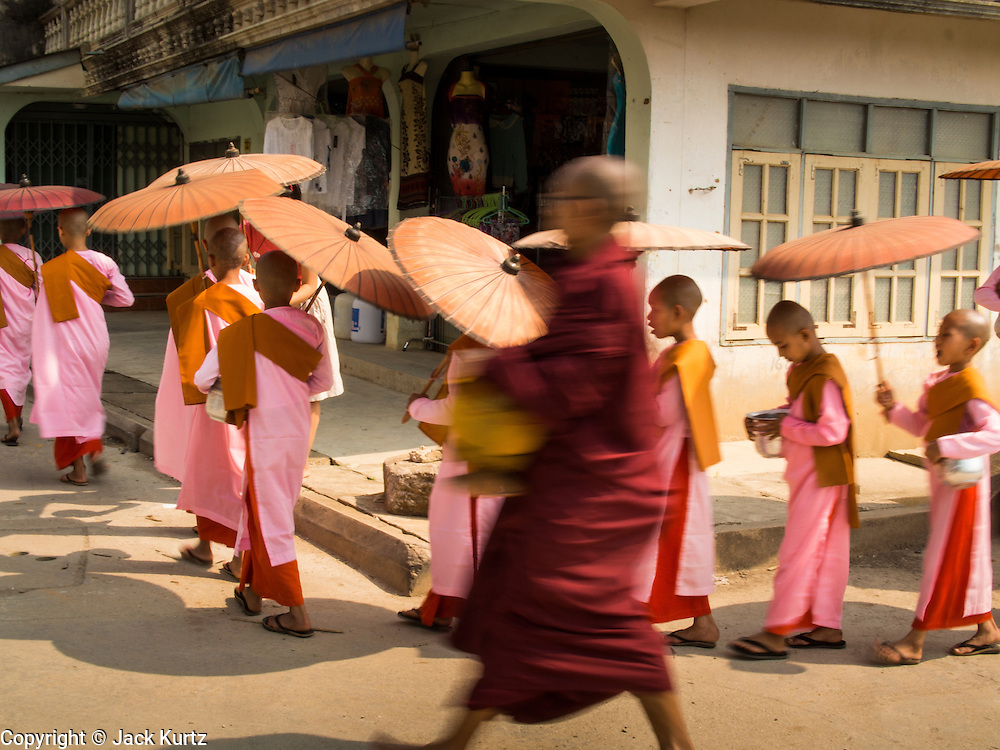 "26 APRIL 2014 - TACHILEIK, SHAN STATE, MYANMAR: A Buddhist monk walks past Buddhist  nuns on their alms rounds in the morning in Tachileik, Shan State, Myanmar (Burma). There are about 75,000 Burmese women living as nuns, sometimes called ""Bhikkhuni"" although the term has fallen out of favor since Bhikkhuni are no longer ordained. Many of the women who become nuns do so to escape poverty or abuse.  PHOTO BY JACK KURTZ"