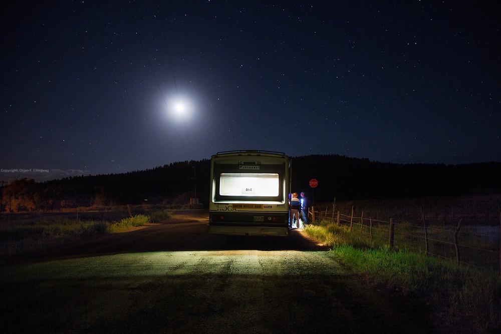 Wolfs Creek, CO, USA, 20130614: Meurig James (464) må stoppe rett før den kraftige stigningen opp til Wolf Creek på grunn av kraftige fordøyelsesproblemer. Nattskiftet med kona blir kalt inn tidlig for å hjelpe til med å stable ham på hjula. Etter flere timers søvn, oksygen og intra venøs væske blir han stablet på sykkelen igjen, like blid.