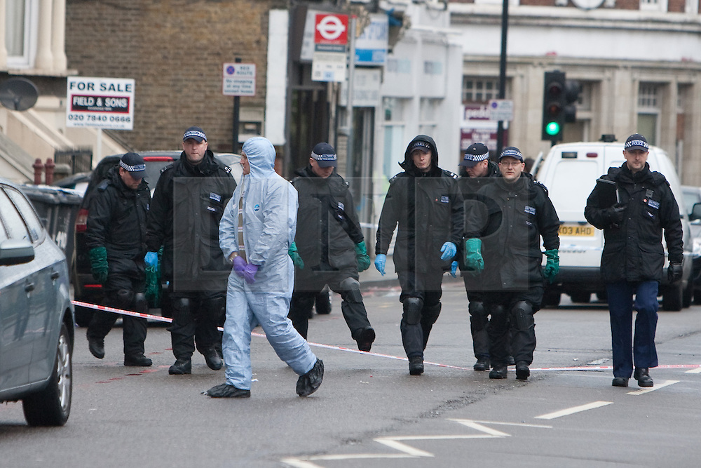 © under license to London News Pictures. 30/03/2011.  Police forensic officers investigate the Stockwell Food & Wine shop, Stockwell Road, Brixton where a 5 year old girl and a 35 year old man were shot last night. . Photo credit should read LNP..
