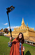 Laos, Vientiane. Pha That Luang. Tourist taking a selfie with a smart phone on a selfie stick.