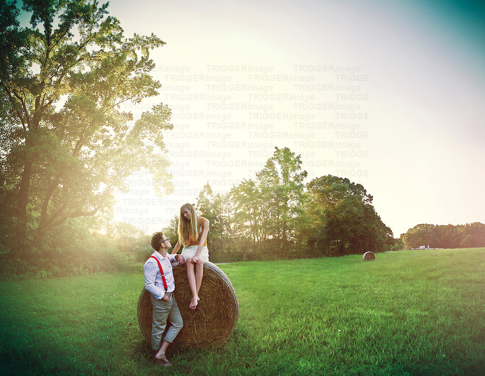 young couple in a field, girl sitting on a hay bail as young man wearing red braces flirts looking at young woman
