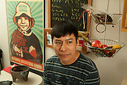 Victor Hernandez in Irwin Sanchez's kitchen. On the table beside him is a traditional molcajete, or mortar.