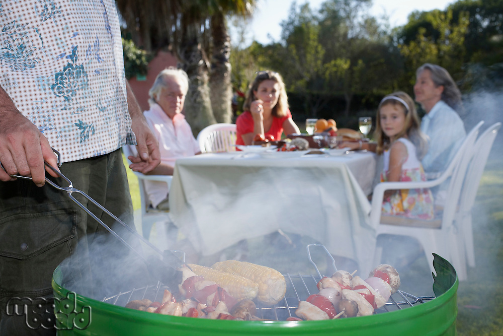 Man grilling other family members sitting at table in background close-up