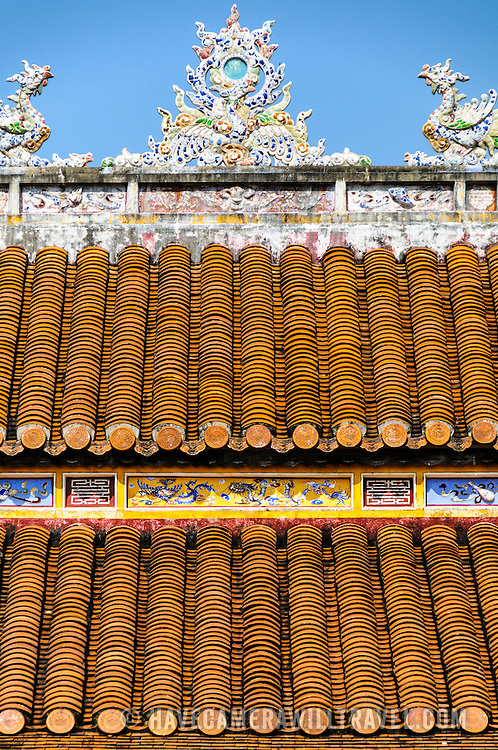 A decorated roof at a restored building at the Imperial City in Hue, Vietnam. A self-enclosed and fortified palace, the complex includes the Purple Forbidden City, which was the inner sanctum of the imperial household, as well as temples, courtyards, gardens, and other buildings. Much of the Imperial City was damaged or destroyed during the Vietnam War. It is now designated as a UNESCO World Heritage site.
