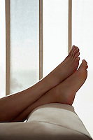 Woman resting with feet up on sofa in living room close up of feet low section