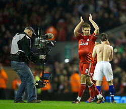 LIVERPOOL, ENGLAND - Tuesday, March 13, 2012: Liverpool's hat-trick hero captain Steven Gerrard celebrates with the match-ball tucked under his red jersey after a magnificent 3-0 thrashing of city neighbours Everton during the Premiership match at Anfield. Gerrard, on his 400th Premier League appearance, became the first player since Ian Rush in 1982 to score a hat-trick in a Merseyside Derby. (Pic by David Rawcliffe/Propaganda)