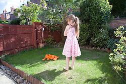 Little girl sulking in the garden,
