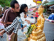 "26 JUNE 2011 - CHIANG MAI, THAILAND:  A man helps his daughter bathe a statue of the Buddha to ""make merit"" in the ""Walking Street"" market in Chiang Mai, Thailand. The Walking Street market is a weekly, Sunday night, market along Ratchadamnoen Street in Chiang Mai.   PHOTO BY JACK KURTZ"