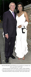 MR & MRS BRUCE FORSYTH at a party in London on 4th July 2001.	OPY 332