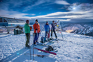 After skinning up Buttermilk Mountain a group of skiers prepare to ski back down in the moonlight in Aspen, Colorado.
