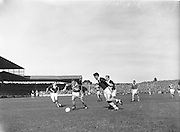 Kerry's D. Geaney crashes through the Galway defence pursued by Galway's S Colleran and F Erens during the All Ireland Senior Gaelic Football Championship Final, Kerry vs Galway in Croke Park on the 27th September 1959. Kerry 3-7 Galway 1-4.