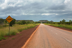 A shaft of sunlight lights the road near the Erskine Range on the road to Fitzroy Crossing in the wet season.