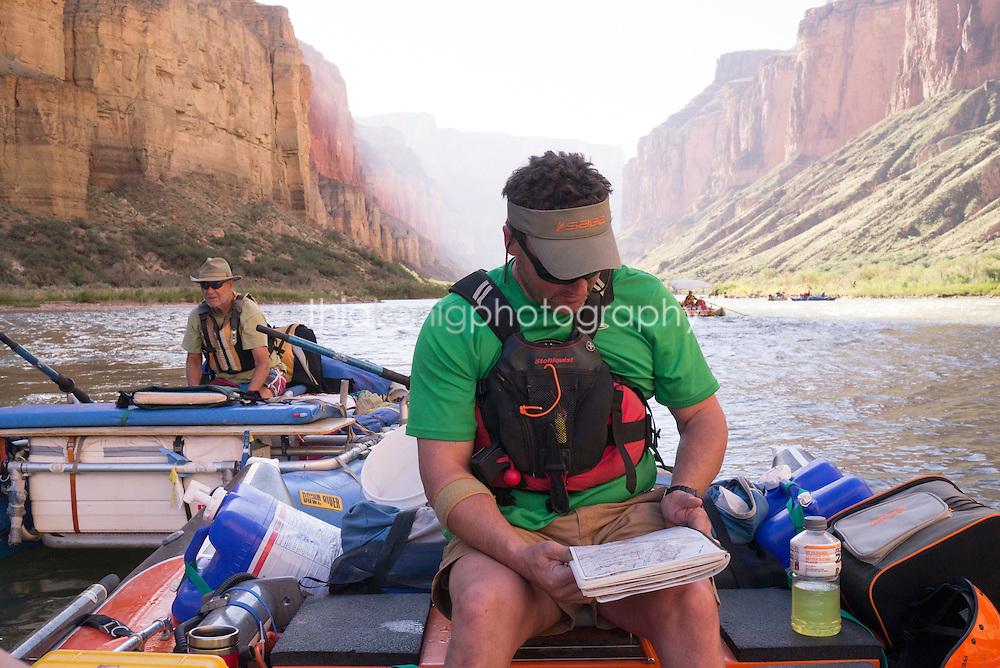 Boatman pauses to read a river map, Colorado River, Grand Canyon, AZ