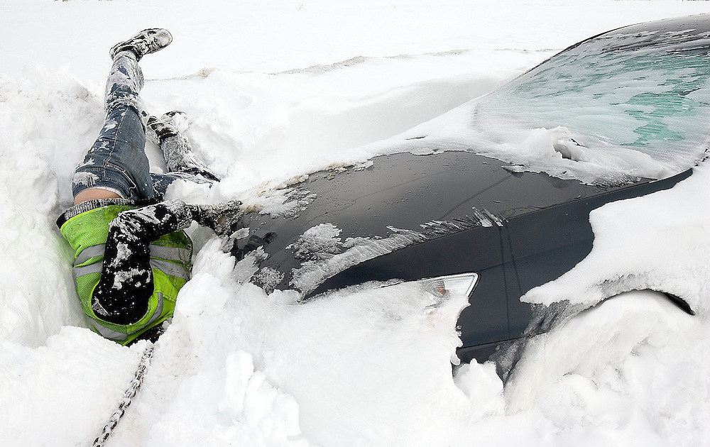 Marc Palmer of Two Dudes Towing out of Lindon, Utah hangs upside down to try and attach a chain to this Honda Accord to pull it from the snow drift. This and other cars were trapped overnight by a fierce blizzard that hit the Utah County area Wednesday night. Photo taken in Highland, Utah Thursday Feb. 14, 2008. August MIller/ Deseret Morning News .