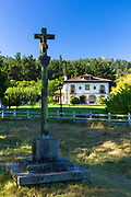 Christian crucifix of Jesus Christ with stylish hacienda house behind in Liendo, Cantabria, Spain