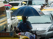 "16 SEPTEMBER 2015 - BANGKOK, THAILAND:  A man under an umbrella rides his motorized trike during a rainstorm in Bangkok. The remnants of tropical storm ""Vamco"" hit Bangkok Wednesday. The storm, downgraded to a tropical depression, brought bands of rain to central Thailand, including Bangkok. The Thai Meteorological Department said the storm would help alleviate the drought that has gripped Thailand since late last year.    PHOTO BY JACK KURTZ"
