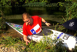 Stock photo of a woman examining shore vegetation from her kayak