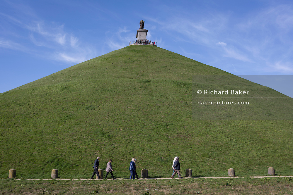 Visitors tour conical 43 metre high Waterloo Lion's battlefield Mound, on 25th March 2017, at Waterloo, Belgium. The Lion's Mound (Butte du Lion is a large conical artificial hill completed in 1826. It commemorates the location on the battlefield of Waterloo where a musket ball hit the shoulder of William II of the Netherlands (the Prince of Orange) and knocked him from his horse during the battle. From the summit, the hill offers a 360 degree vista of the battlefield. The Battle of Waterloo was fought 18 June 1815. A French army under Napoleon Bonaparte was defeated by two of the armies of the Seventh Coalition: an Anglo-led Allied army under the command of the Duke of Wellington, and a Prussian army under the command of Gebhard Leberecht von Blücher, resulting in 41,000 casualties.