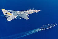 An F-14 Tomcat flies over the aircraft carrier USS Independence CV-62, during operations in the Pacific.