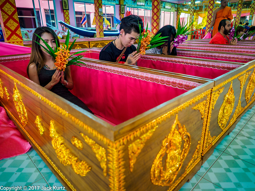 "24 JUNE 2017 - BANG KRUAI, NONTHABURI: People sit up in their coffins after being reincarnated during a ""resurrection"" or rebirthing ceremony at Wat Ta Kien (also spelled Wat Tahkian), a Buddhist temple in the suburbs of Bangkok. People go to the temple to participate in a ""Resurrection Ceremony."" Thai Buddhists believe that connecting people by strings around their heads, which are connected to a web of strings suspended from the ceiling, amplifies the power of the prayer. Groups of people meet and pray with the temple's Buddhist monks. Then they lie in coffins, the monks pull a pink sheet over them, symbolizing their ritualistic death. The sheet is then pulled back, and people sit up in the coffin, symbolizing their ritualist rebirth. The ceremony is supposed to expunge bad karma and bad luck from a person's life and also get people used to the idea of the inevitability of death. Most times, one person lays in one coffin, but there is family sized coffin that can accommodate up to six people. The temple has been doing the resurrection ceremonies for about nine years.     PHOTO BY JACK KURTZ"