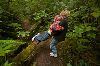 Russell Laman (age 5) helps his little sister Jessica (age 2) over a log on a hike in Olympic National Park, Washington.