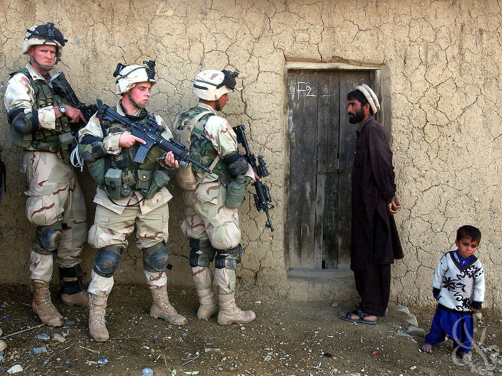 An Afghan man and his son watch as soldiers from the US Army 82nd Airborne Division prepare to sweep their home in southeastern Afghanistan November 07, 2002. Soldiers discovered over a dozen mines and grenades,  14 rocket propelled grenades, and plastic explosives as they searched several compounds as part of Operation Alamo Sweep.