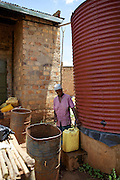 One of Nusula Ssewanonda neighbours comes to buy water from her tank. Nusula is a member of Kirangira Womens group in Mukono District, Uganda. She recently sold a bull calf and has invested the money in drainpipes and a big water tank. She now collects rainwater from the roof of her house and sells it to people in her village. She then used this money to install bio gas.