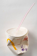 a crumbled McDonald's paper cup with plastic straw