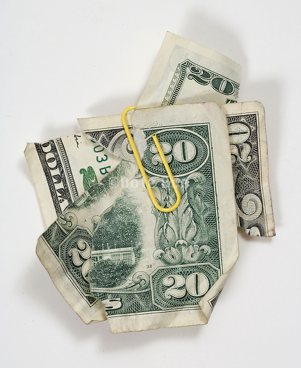torn up 20 dollar bills hold together with a yellow paperclip