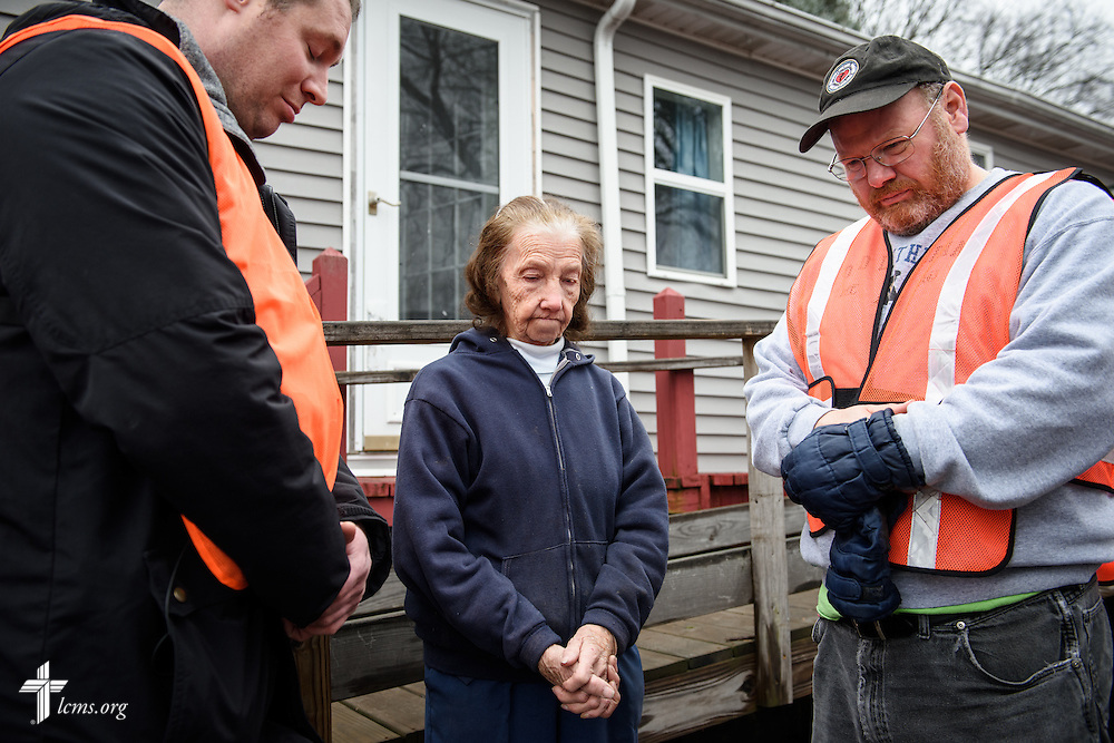 The Rev. Donald Love (right), pastor at Calvary Lutheran Church in Watseka, Ill., and the Rev. Michael Meyer, manager of LCMS Disaster Response, pray with Mini Kessinger, an 88 year-old parishioner affected by a recent flood, while teams clean flood-damaged homes on Saturday, Jan. 9, 2016, in Watseka. A flood at the end of December ravaged over a 60-block radius of the town. LCMS Communications/Erik M. Lunsford