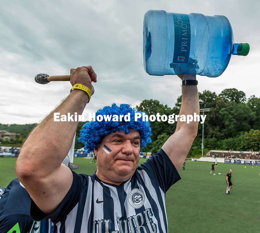 Rob Corley cheers with the South Slope Blues before the game. The Men's Asheville City Soccer Club lost to Greenville Football Club 1-0  in Memorial Stadium in Asheville, NC on June 23, 2018.