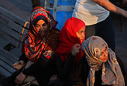 Three young Turkish women seated on a bench near the Eminonu quayside, Istanbul, Marmara, Turkey. Eminonu is on the South bank of the Golden Horn at the Southern end of the Galata bridge. Picture by Manuel Cohen