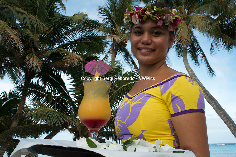Rarotonga Island. Cook Island. Polynesia. South Pacific Ocean. A waitress serves delicious next to the poolside at the luxurious Little Polynesian Resort in Rarotonga. Nestled on the southern tip of Rarotonga, Little Polynesian Resort is a sophisticated playground for grown-ups. Here, serenity is certain, seclusion is guaranteed, and romance is everywhere. This is a Resort of unpretentious luxury where idyllic beaches beckon. The Beachfront Ares offer an uninterrupted vista of the azure lagoon while the view of tropical gardens from the garden thatched Ares is just as dazzling. Welcoming guests over the age of 15 years only, the primary clientele of the Resort are honeymooners and couples. Set on an unspoilt beach, the Resorts dwellings ooze Polynesian charm and luxury. Spend your days roaming the beaches and sipping fresh-fruit cocktails by the pool. Traditional architecture complements the island's natural beauty, and the bungalows are designed with every modern luxury, from gazebos with daybeds to outdoor showers. Experience the epitome of Polynesian luxury in our well-appointed beach and garden accommodations. The romance of traditional Polynesian architecture meets the creature comforts of the West in our modern interpretations of the local dwellings, or Are as they are known. Rendered in a minimalist palette of ivory and local woods, the spare elegance of our rooms takes the romance quotient up a notch. Traditional accents such as Wild Hibiscus, Mangaian (coconut) sinnet weaving on beams as well as a thatched roof with natural pandanus add to the ambience of our South Seas paradise. The Little Polynesian offers all the amenities one would expect from the Cook Islands' most upscale boutique resort. Our overbeach Ares (bungalows) promise aimless days of looking out to the lagoon's turquoise waters and waking up to the gentle sound of waves, while the scent of tropical flowers fills the air around our Pia Tiare (garden units). Whichever you choose, we guara