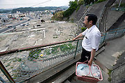 Dr. Sen Hiraizumi poses for a photo outside the Yamada  town Prefectural Hospital in Yamada town, Iwate Prefecture, Japan on  10 June 20011.  .Photographer: Robert GilhoolyDr. Sen Hiraizumi passes through debris on his way from  visiting a patient in Yamada town, Iwate Prefecture, Japan on  10 June 20011. With the prefectural hospital in Yamada badly damaged by the March 11 quake and tsunamis, hospital staff have followed Hiraizumi's lead to take their expertise to those in need..Photographer: Robert Gilhooly