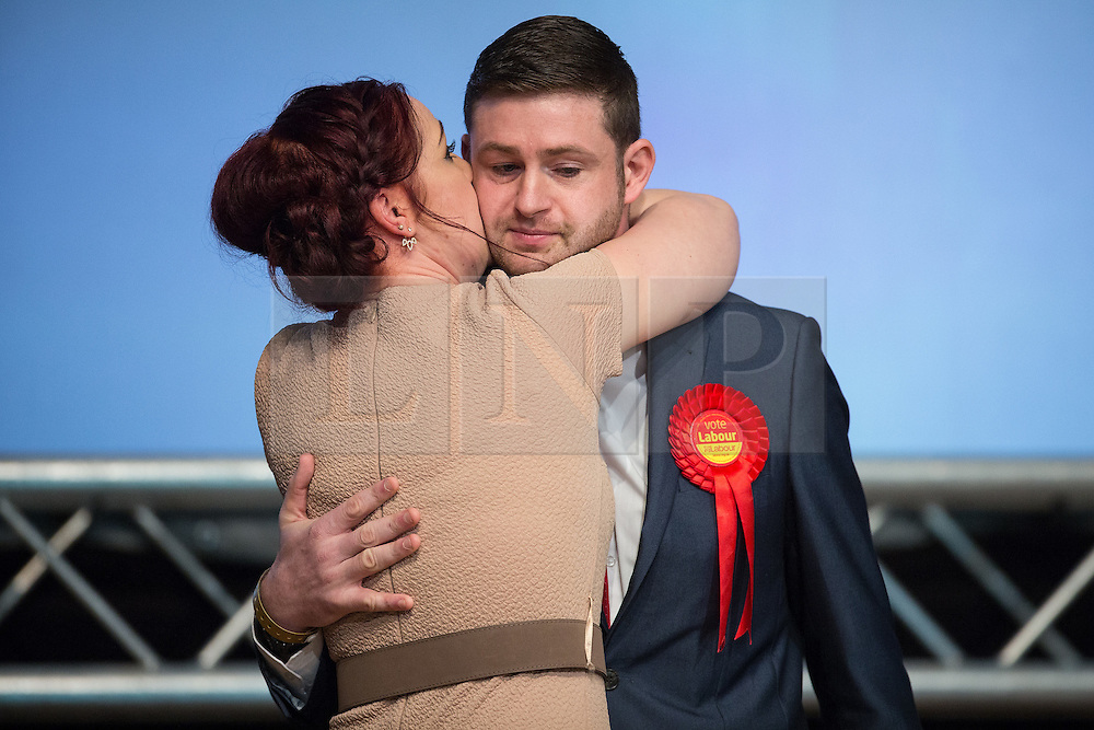© Licensed to London News Pictures . 04/12/2015 . Oldham , UK . Labour candidate JIM MCMAHON kisses his wife CHARLENE after being declared the victor at the count at the Oldham West and Royton by-election , at the Queen Elizabeth Hall in Oldham . The by-election was called following the death of MP Michael Meacher . Photo credit : Joel Goodman/LNP