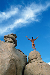 Naked man with arms outstretched while standing on top of rocks