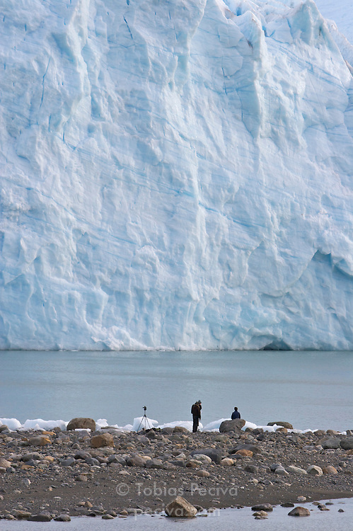A group of hikers stand at the terminal face of the Perito Moreno Glacier. The glacier is a popular hiking destination in Los Glaciares National Park, Argentina.