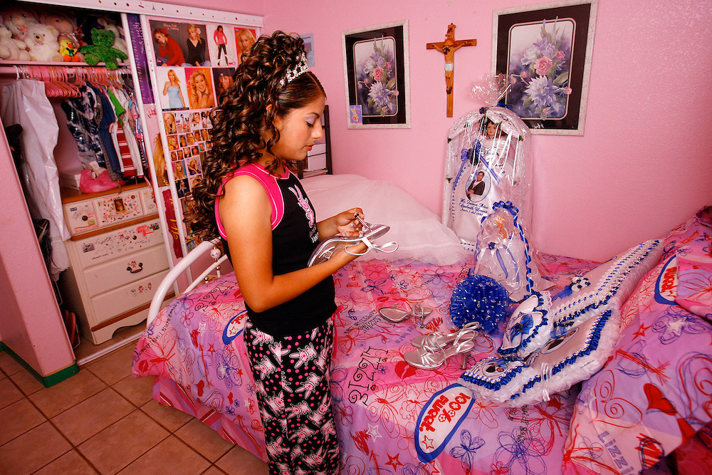 Elizabeth Ureña places her high heels and other items for her quinceañera on her bed before the ceremony. It is the first day that Elizabeth is allowed to wear make-up and high heels.