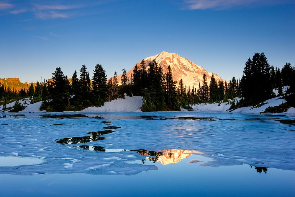 The sun sets over Mount Rainier and Unice Lake in Mount Rainier National Park.