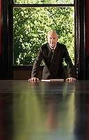 Man leaning on Conference Table greenery behind