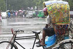 June 12, 2017 - Dhaka, Bangladesh - A Rickshaw puller takes shelter inside of a Rickshaw during heavy rain at Dhaka, Bangladesh, June 12, 2017. (Credit Image: © Suvra Kanti Das via ZUMA Wire)