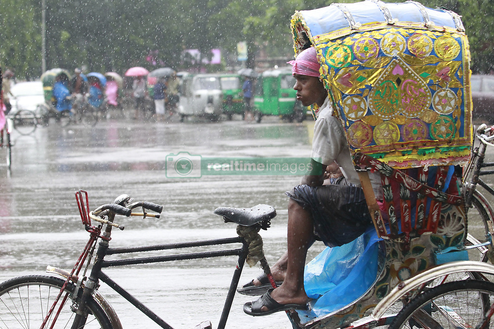 June 12, 2017 - Dhaka, Bangladesh - A Rickshaw puller takes shelter inside of a Rickshaw during heavy rain at Dhaka, Bangladesh, June 12, 2017. (Credit Image: © Suvra Kanti Das via ZUMA Wire)