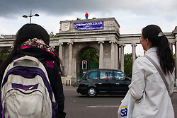 London, August 12th 2014. Tourists look on as protesters from Fathers For Justice demonstrate against separation from their children from the top of   Decimus Burton's Ionic screen entrance to Hyde Park adjacent to Apsley House at  Hyde Park Corner.