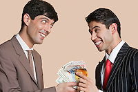Young businessmen smiling while looking at each other with Euros in hand