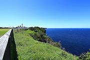 landscape: fenceline perspective along coast line at vaucluse, sydney with landmark lighthouse in background